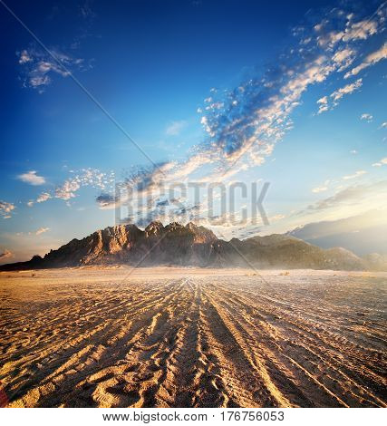 Mountains in sand desert at the sunset