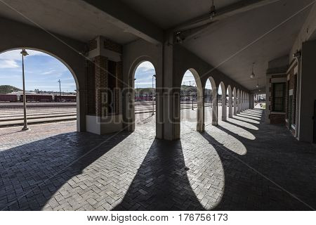 Barstow, California, USA - March 11, 2017:  View of rail tracks from behind the arches at the historic Barstow Harvey House train station in the Mojave Desert.