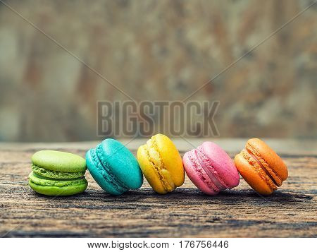 Colorful macarons on vintage pastel background. Macaron or Macaroon is sweet meringue-based confection. poster