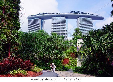 Singapore, Singapore - February 12, 2017: People walk in the Gardens by the Bay near Marina Bay Sands on sunny day in Singapore.