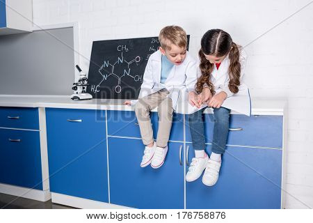 Little boy and girl in white coats playing in chemical laboratory