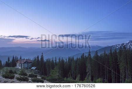 House at a mountain hill at sunrise. Hut in a forest with view at a mountain range at sunrise