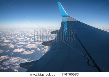 View at the airplane wing over curly clouds