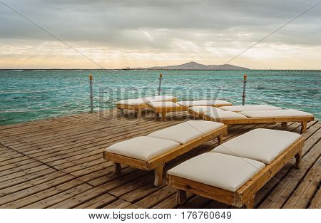 Pier with chaise longues in the sea in resort. Summer vacation. View at a distant island at sunrise.
