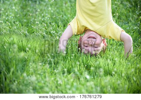 Portraits of happy kids playing upside down outdoors in summer park. Happy smiling kid boy child