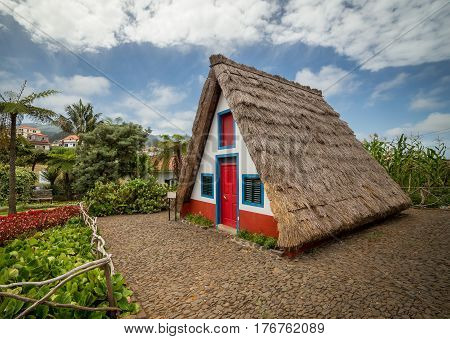 Traditiona house of Madeira. Thatched roof in characteristic traingle shape. House is surrounded by intense flowers from nearby garden