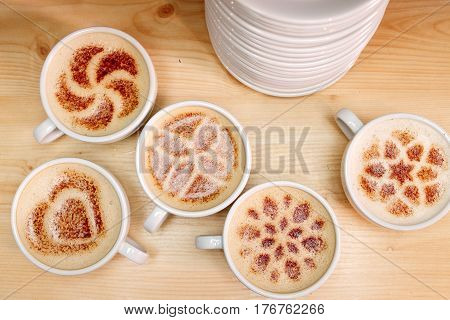 A lot of cups of coffee and a plate with a fire. Cappuccino coffee. A cup of latte, cappuccino or espresso coffee with milk put on a wood table. Drawing the foam milk on top.