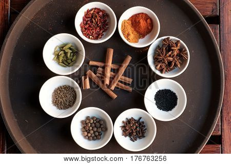 Many different spices on white plates, neatly laid out on a round tray. Cinnamon sticks in the middle of seasonings