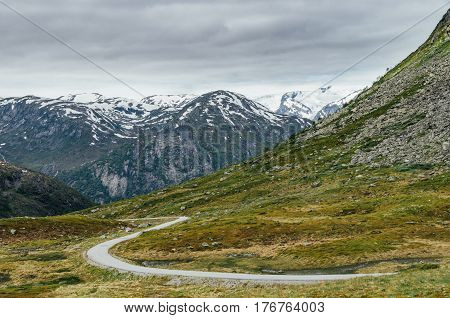 Narrow winding road in mountains norwegian tundra landscape