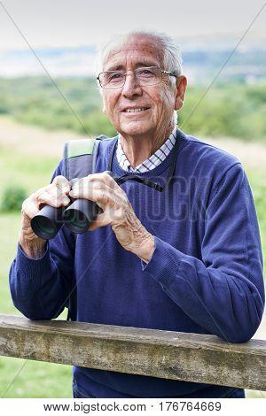 Senior Man On Walk With Binoculars In Countryside