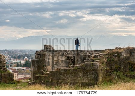 KUTAISI, GEORGIA, NOVEMBER, 05: Man standing on the ruins of the ancient fortress in Georgia, Kutaisi, overlooking the city on nowember, 05, 2016 in Georgia