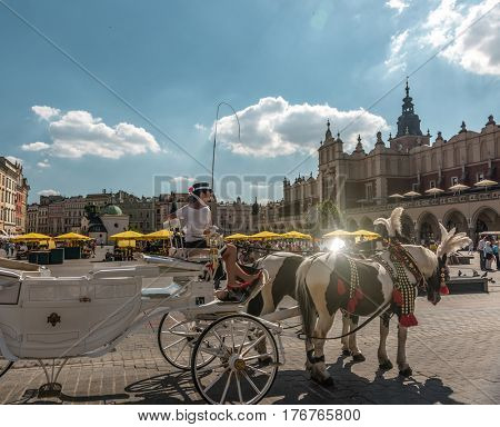 POLAND, KRAKOW- JULY 02: Carriage with beautiful horses near a lovely ancient square, gothic building on the background in Krakow Poland on July 02, 2015