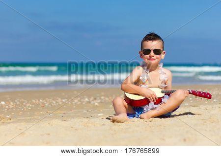 Little happy boy have fun, play music on Hawaiian guitar , enjoying sun  ocean beach. Children healthy lifestyle. Travel, family activity on tropical island summer holiday