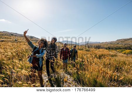 Group Of Friends Taking Photograph On Country Walk