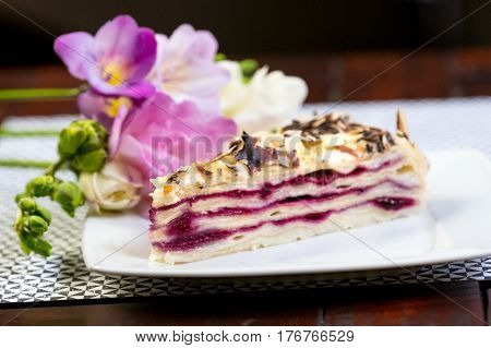 Piece of delicious cake Blueberry Vanilla Cake Piece of cake on a white plate with flowers close-up on a wooden table.