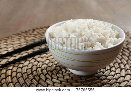 Bowl of rice and chopsticks on wicker mat
