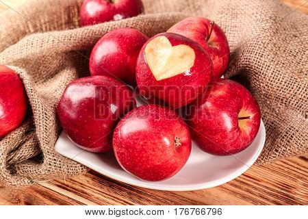Plate in shape of heart with fresh red apples on wooden table
