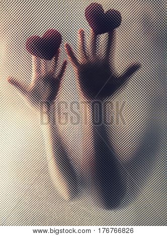 Hands of young couple with hearts behind riffled glass