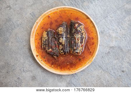 Fried mackerel in chilli sauce is made of sweet and spicy chili sauce poured into fried mackerels on wooden dish