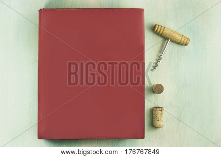A mockup with a vibrant pink book, a corkscrew, and wine corks, shot from above on a teal background with a place for text
