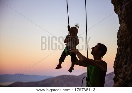 Rock climber giving a swing to his little daughter in safety harness hanging on rope