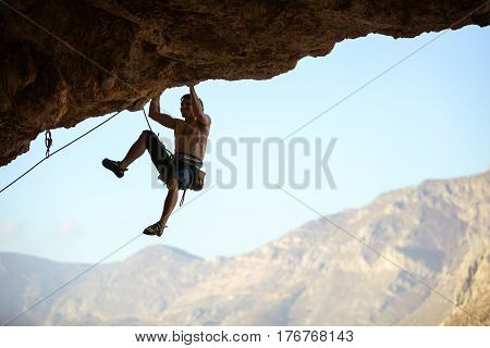 Young Caucasian man struggling to climb ledge on natural cliff