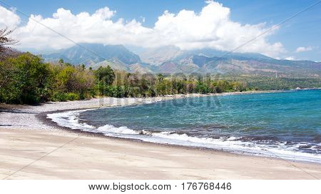 Empty white sand beach and clear blue ocean waves at Bajawa Ruting Flores in the morning combined with mountains and white clouds at the background.