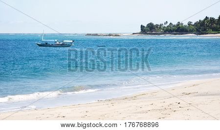 Empty boat at a white sand beach and clear blue ocean waves at Flores.