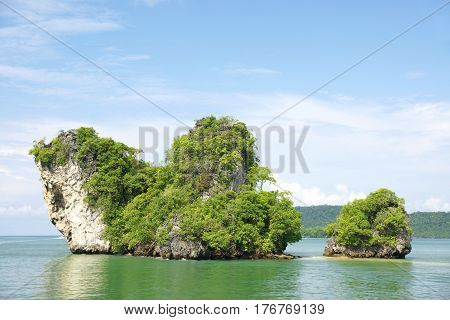 Horizon view of a big horizontal rock cliff with green vegetation surrounded by turquoise blue colored ocean water at midday Krabi Thailand.