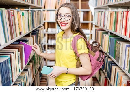 Young happy and enthusiastic female student searching books on the shelves at the library