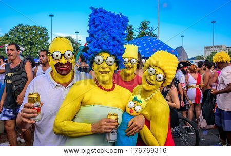 RIO DE JANEIRO, BRAZIL - FEBRUARY 28, 2017: Costumed family of the Simpsons with Homer, Marge, Bart, Lisa and Maggie at Bloco Orquestra Voadora in Flamengo Park, Carnaval 2017