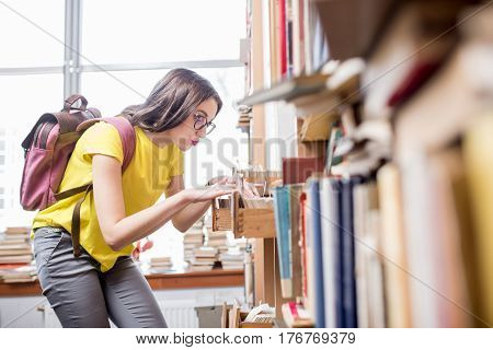 Young student searching books with card catalogue at the old library or archive