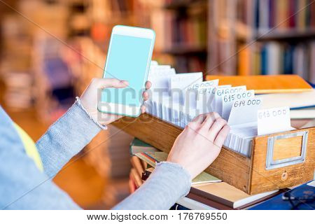 Woman holding smart phone with empty screen near the card catalogue at the library