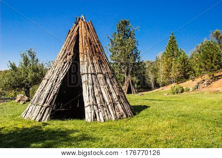 Two American Indian Tepees At Base Of Hill