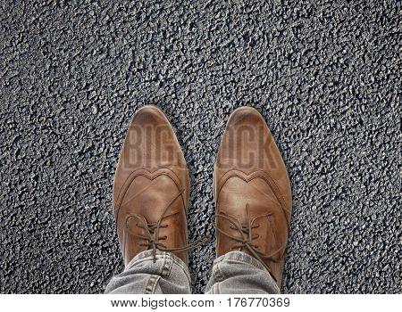 close on shoes wearing bu a young man on asphalt background