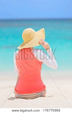 back view of young woman in rashguard and sunhat enjoying the perfect caribbean beach and protecting her skin from sun exposure during summer vacation vacation concept