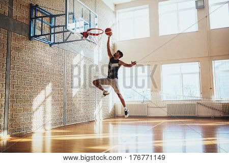 Shot of a young basketball player hammering a ball on the court.