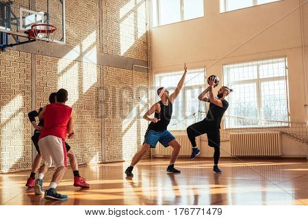 Full length portrait of basketball players playing basketball.