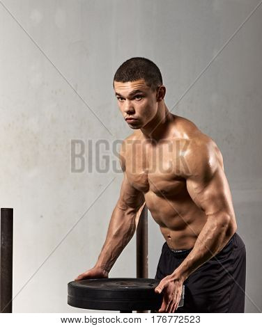 Portrait of strong muscular man holding bumper plate