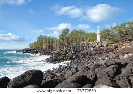 Small concrete lighthouse along rocky shore of Kawaihae Harbour on the leeward side of the Big Island of Hawaii.