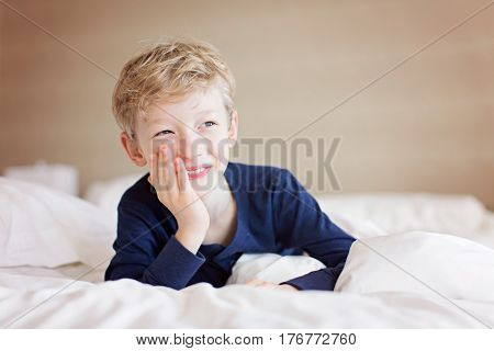 beautiful laughing boy lying in the bed being playful and happy positive emotion concept