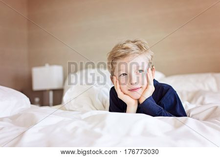 beautiful positive boy lying in bed in hotel room