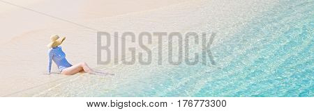 panorama view of young woman in rashguard and sunhat enjoying the perfect caribbean beach and protecting her skin from sun exposure during summer vacation copyspace on the right