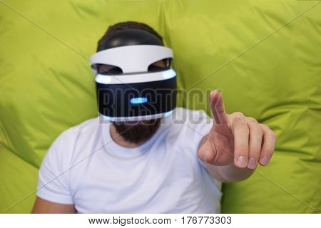 Adult man with beard lying on his back in the virtual glasses on a green background one hand lifted up finger touches cyberspace shallow depth of field selective focus