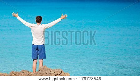 panorama of young man in rashguard and swimming shorts holding hands wide open and enjoying view of beautiful turquoise sea at perfect caribbean island copyspace on right