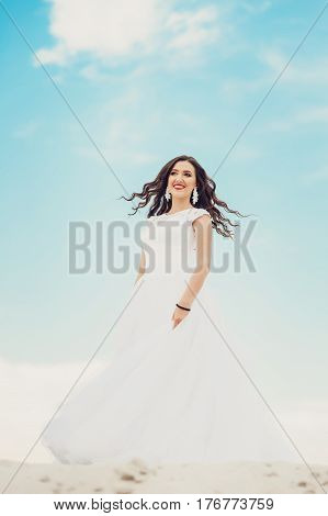 Young stylish smiling brunette woman running in fashionable wedding dress against the blue summer sky on her wedding day. portrait of beautiful bride with long brown curly hair on the beach