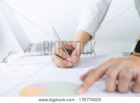 Office worker is pointing and analyzing paper chart infomation for management