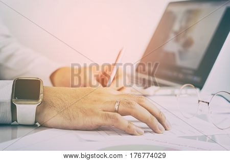 Office worker is analyzing paper and chart infomation in vinatge tone