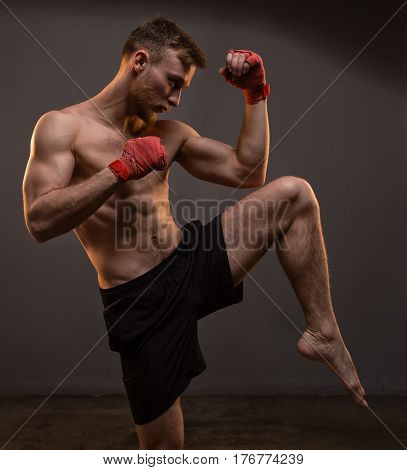 Muscular blond man with leg up on gray background