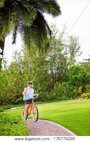 young woman riding bike during vacation at tropical island